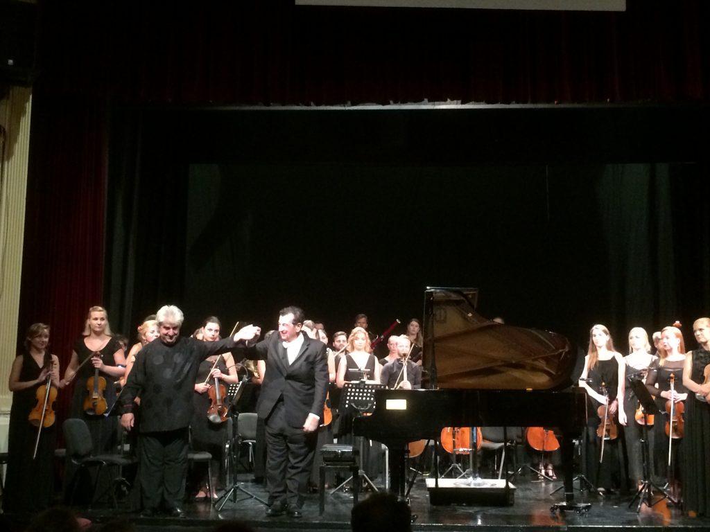 Ο πιανίστας Μάριος Παπαδόπουλος, ο αρχιμουσικός Peter Tiboris και η ορχήστρα Pan-European Philharmonia της Βαρσοβίας δέχονται τα χειροκροτήματα του κοινού. Φωτο: ΚΠΚΣ.